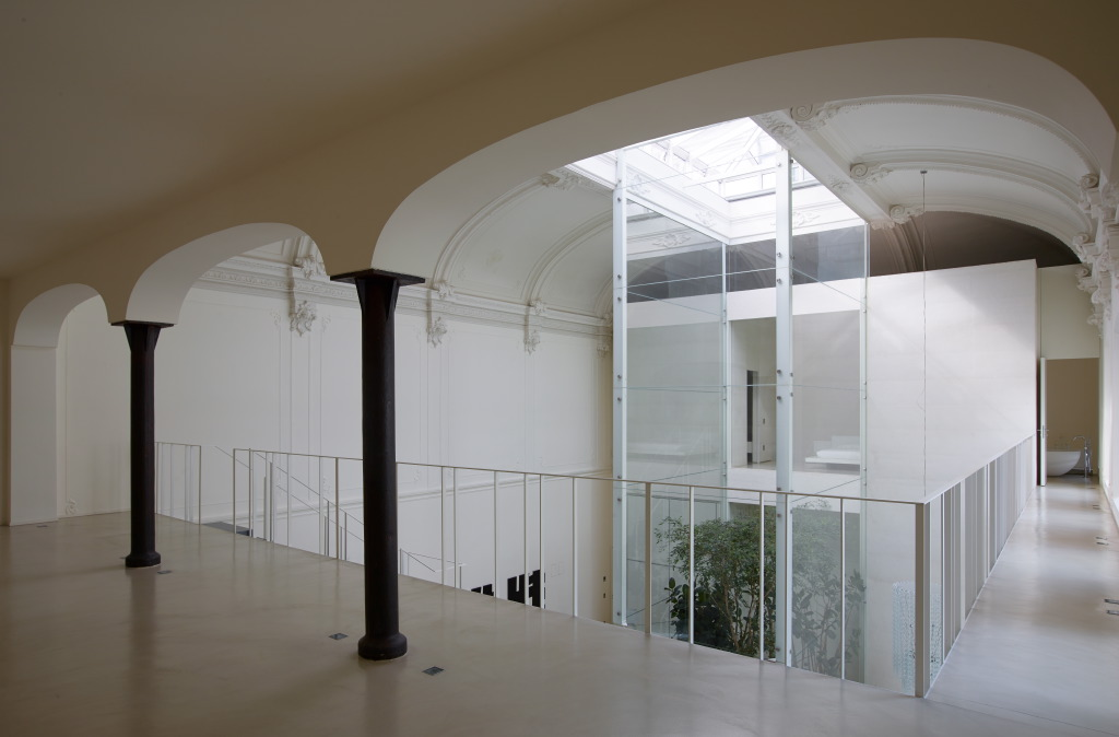 The theatre'soriginal cast iron columns were striped of layers and painted a dark charcoal. A mezzanine levelwalkway provides access to the bedrooms at either endof the building.
