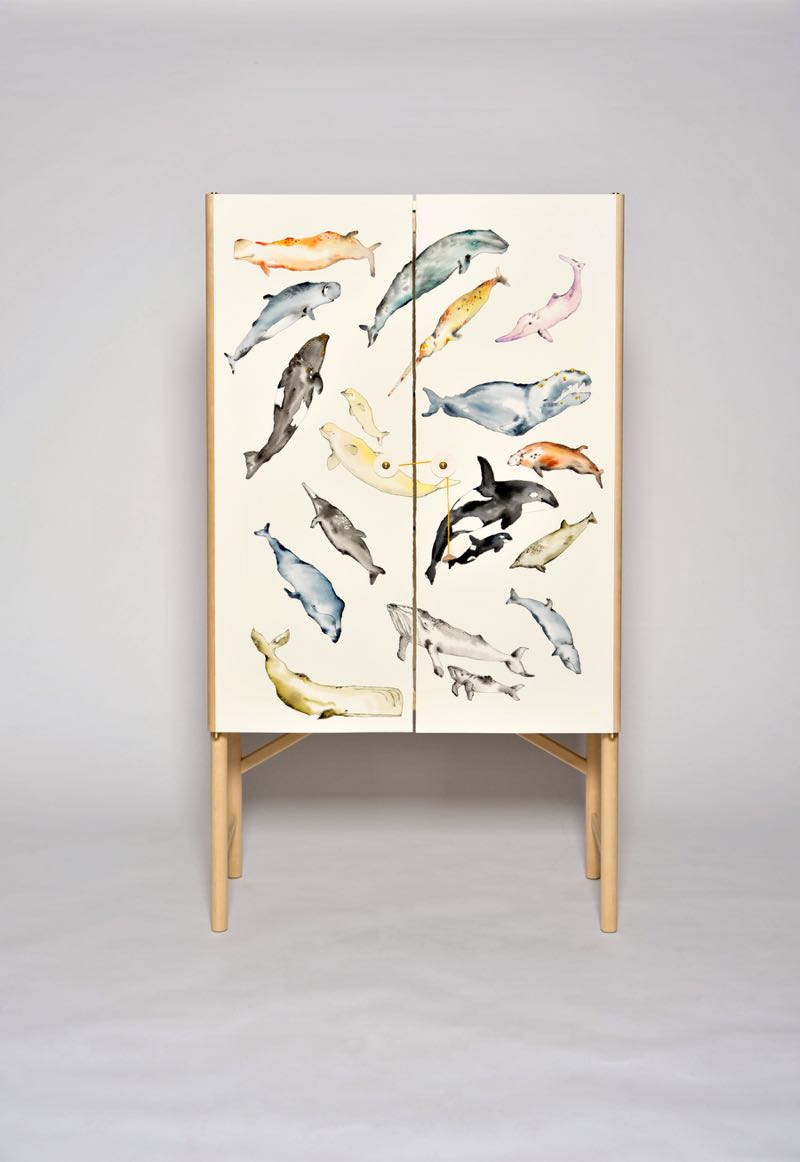 The 'Whale' cabinet designed by Ericsson uses hand painted paper as its door decoration. Wegner's graduation piece when he was a young joiner was acabinet inlaid with hand carved aquariumfish.