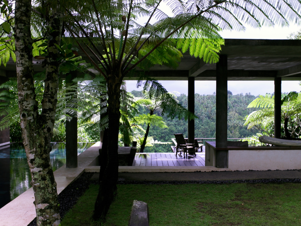 The 'Kuan House' near Ubud looks out onto a jungle forest. Due to the climate much of the house features cool covered areas that catch breezes off surrounding pools of water.