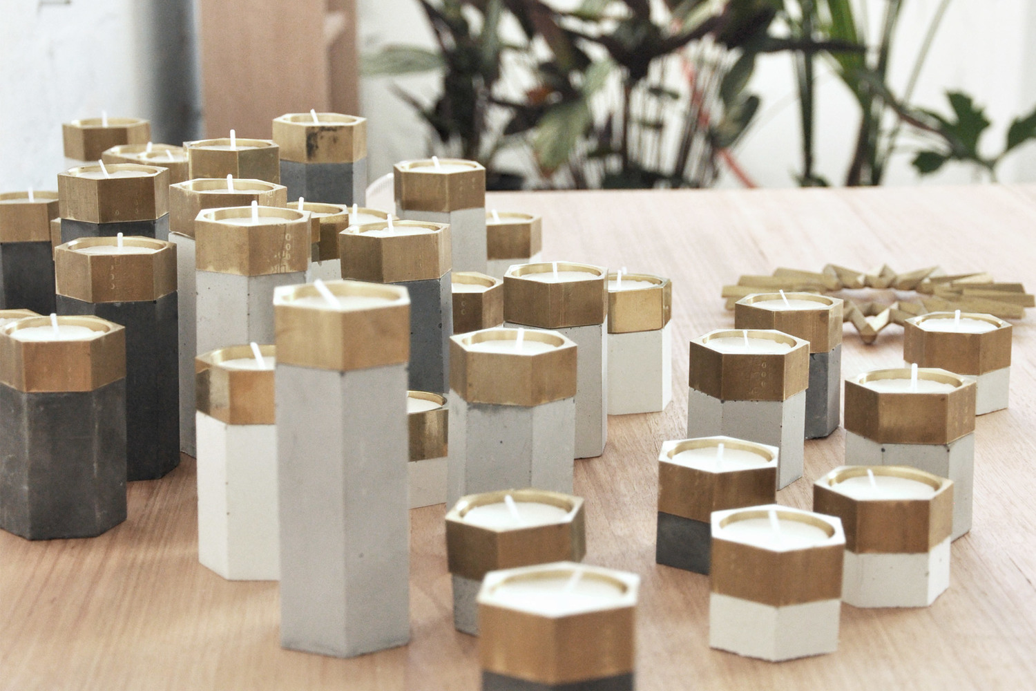 The interlocking 'Hex' candle holders in white or grey concrete and brass by Archier Studio.