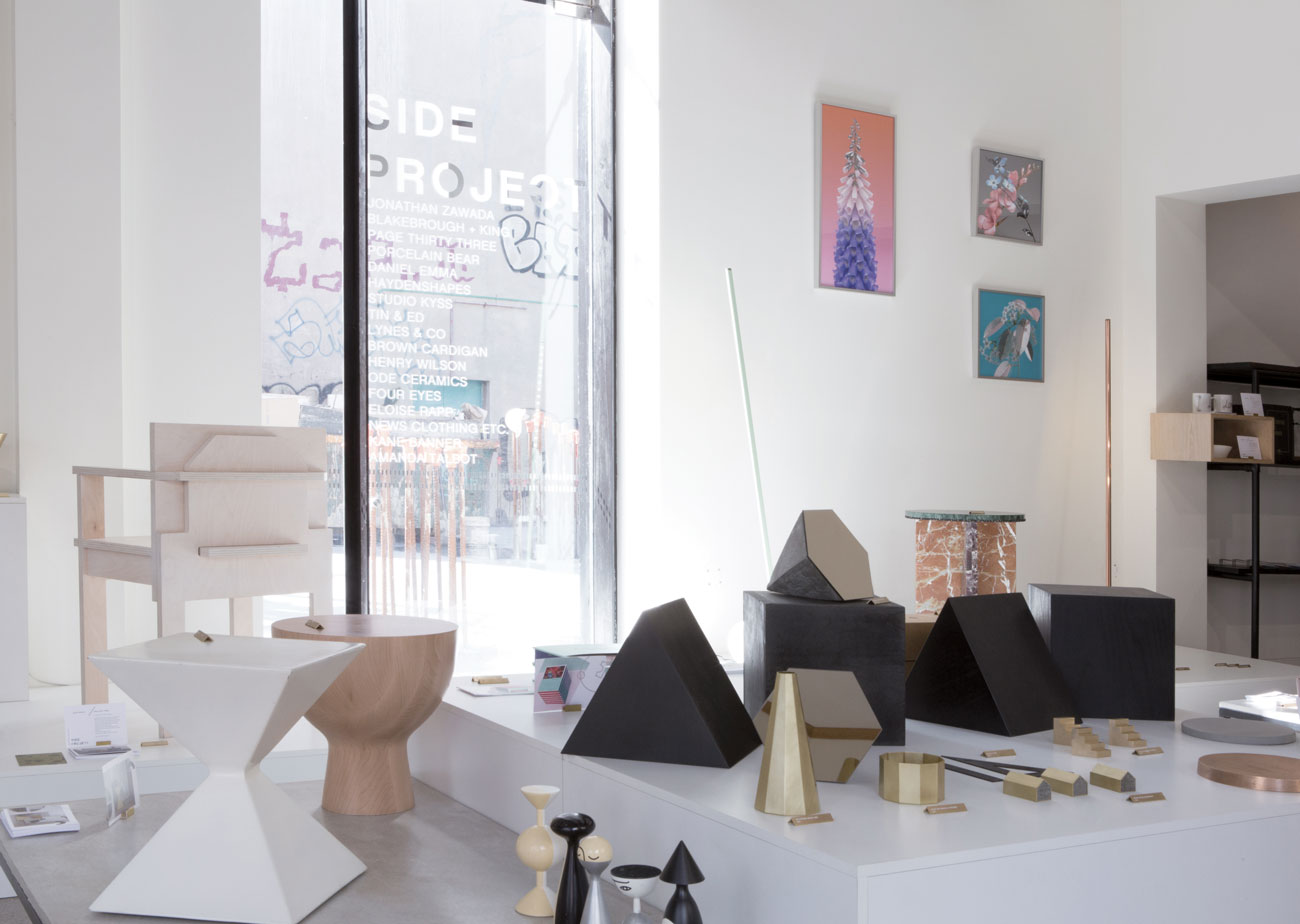 Part of the  Side Project  exhibition - 'Kite' and 'Pod' stools by Blakebrough + King and vessels by Studio Kyss mix it with shapes from Page Thirty Three's 'Neolithic' shelving.