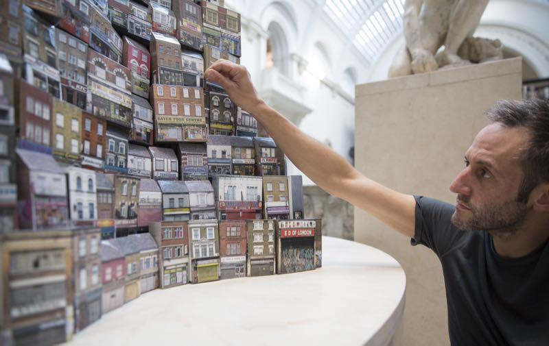 Barnaby Barford pictured with some of the more derelict shops at the base of the 'Tower of Babel' installation made from 3000 individual bone china miniature shops. Photo Ed Reeve.