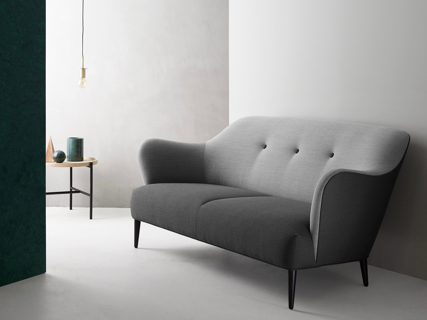 The 'Retro' sofa by 365º North for Won Design. Tightly fitted upholstery in a smooth swooping form.  The brand's 'Cross' side table (also by 365º North) is in the background.