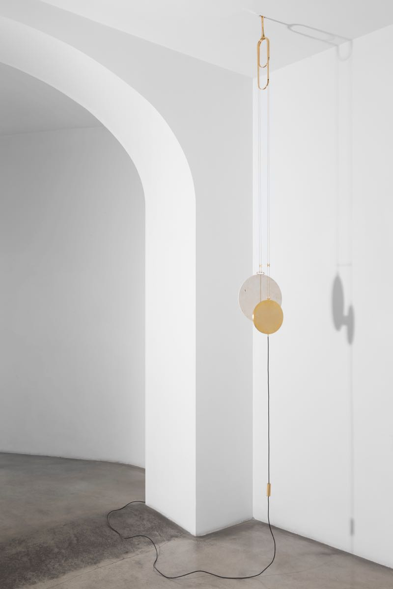 'Eclipse' pendant lamp with a gilded brass light source and travertine disc that softly reflects the light and creates the eclipse.