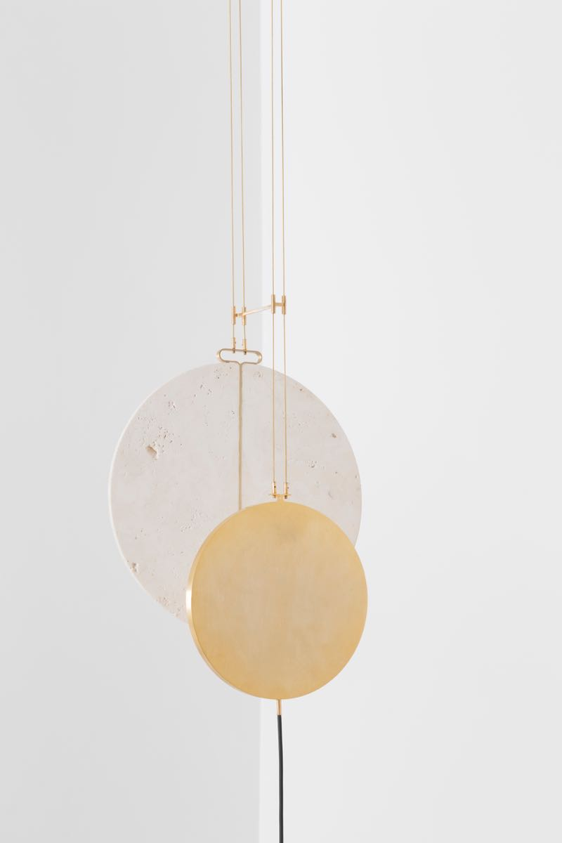 A close-up of the 'Eclipse' pendant lamp showing the travertine disc with central brass strip and gilded guitar strings.