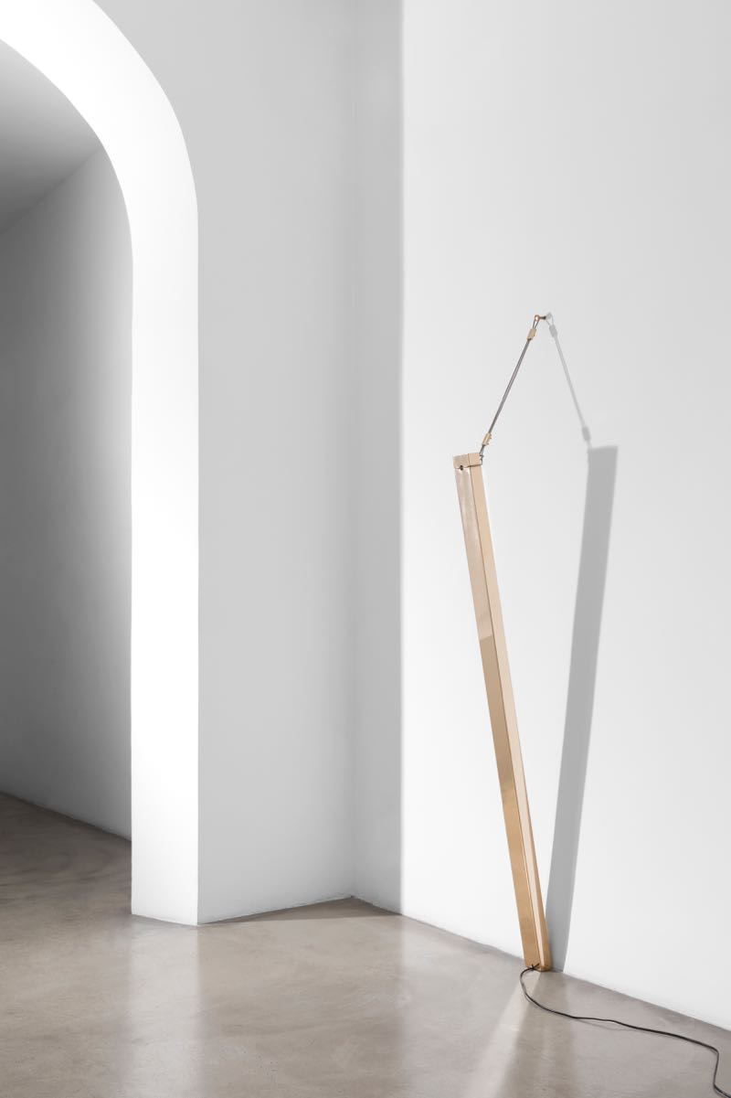 'Regula' a wall mounted LED lamp that is suspended by a steel wire from a lost wax cast nail in the wall. Light is directed onto the wall where it bounces and provides a softer, indirect light.
