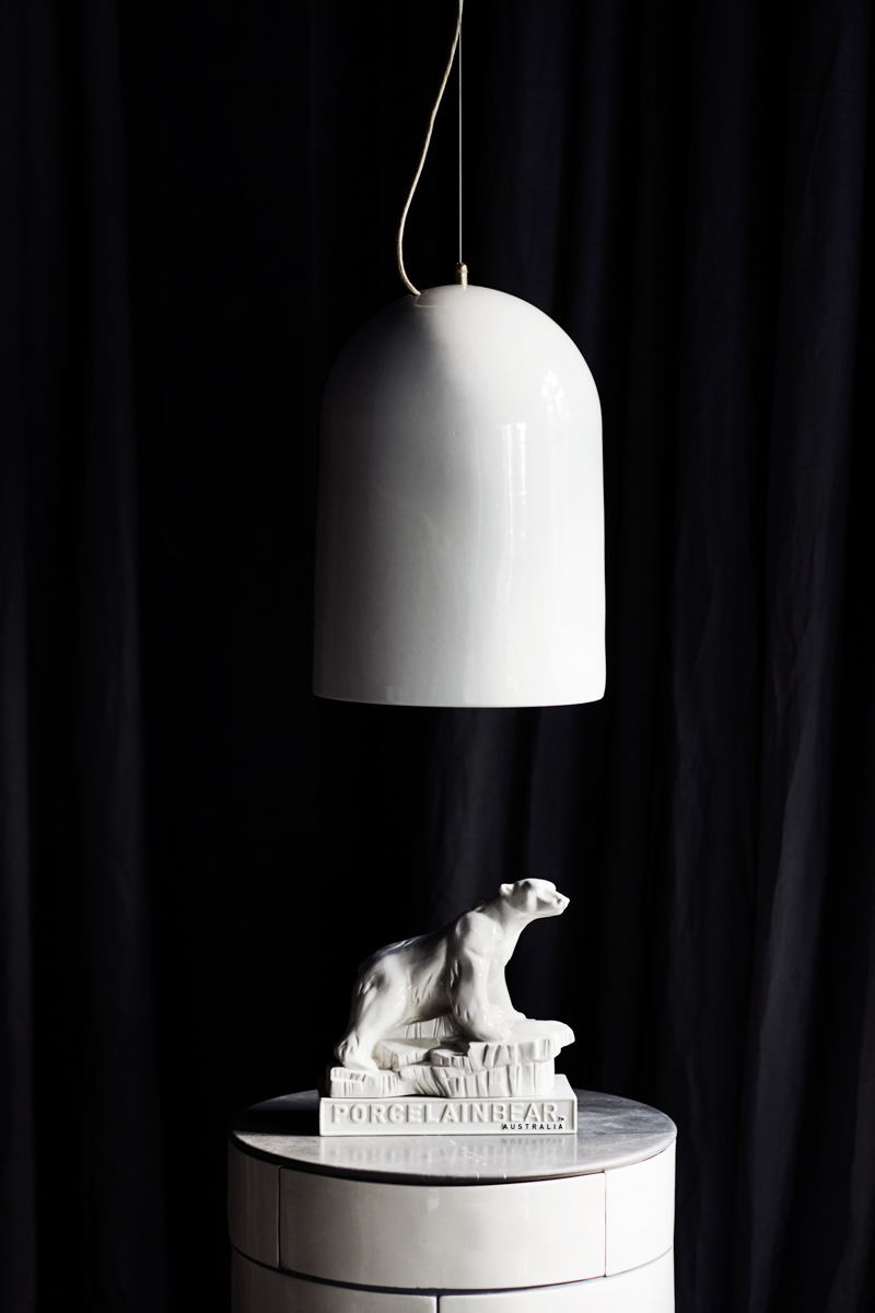 A simple glazed version of the 'Cloche' pendant lamp by Porcelain Bear, hovering over the label's mascot, a polar bear figurine called Percy. 'Cloche' is also available in a crackle glaze and in various other finishes.