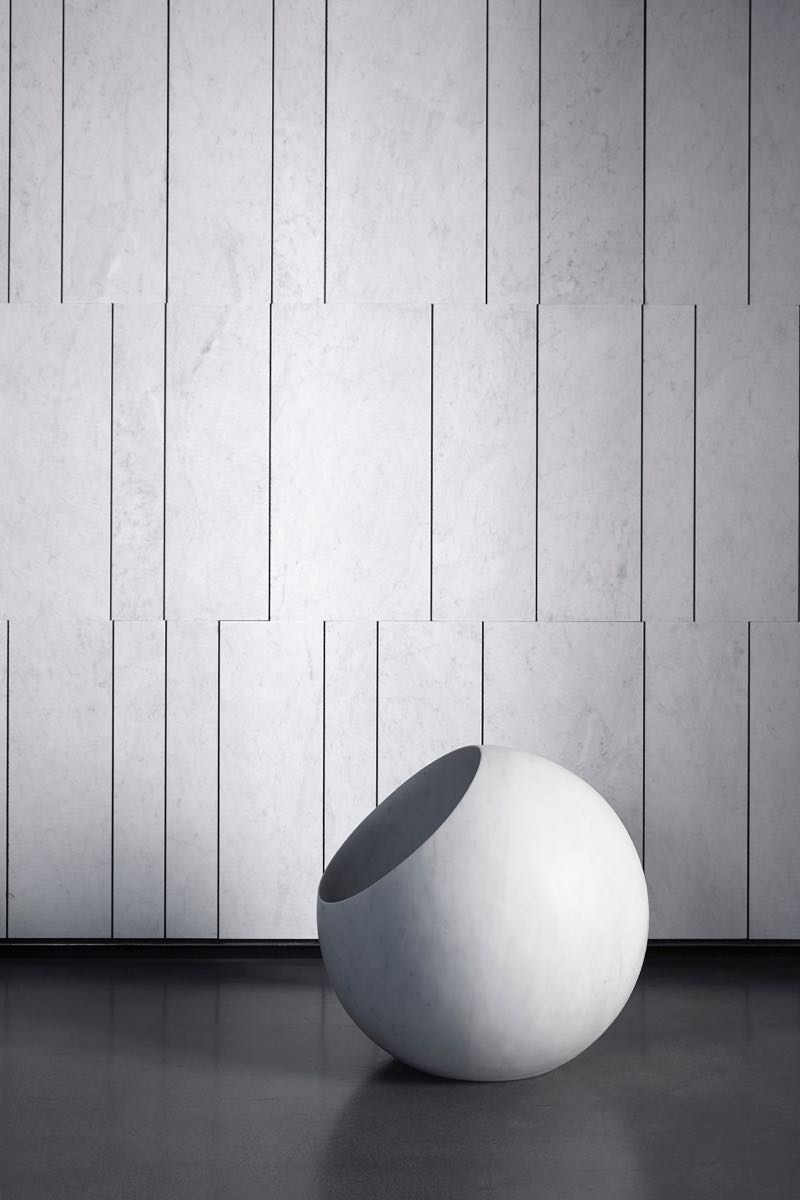 The 'Urano' floor lamp in turned marble by Elisa Ossino for Salvatori. The background is a surface called Cotone Tratti, executed in Carrara marble.