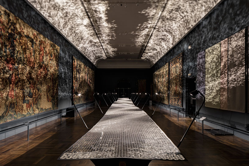 Benjamin Hubert's Layer Studio presented  Foil  in the medieval tapestry room of the V&A. 50,000 hand-applied triangular mirrors made a 20m surface that was motorised to create wave motion.