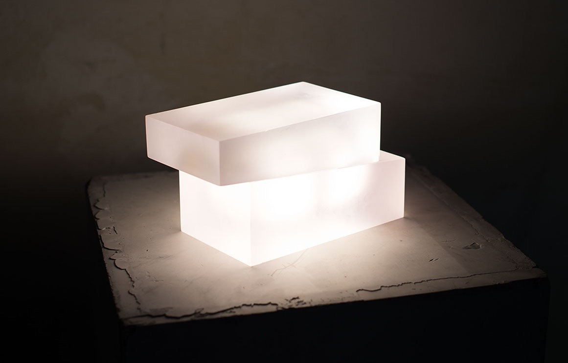 The 'SIBU Dark Matter' table lamp features an on / off mechanism that is triggered by sliding the top block.