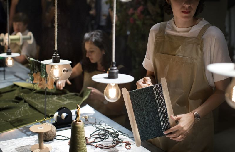 Aimee Betts (foreground) working on her woven textile lighting cables at Makers House.