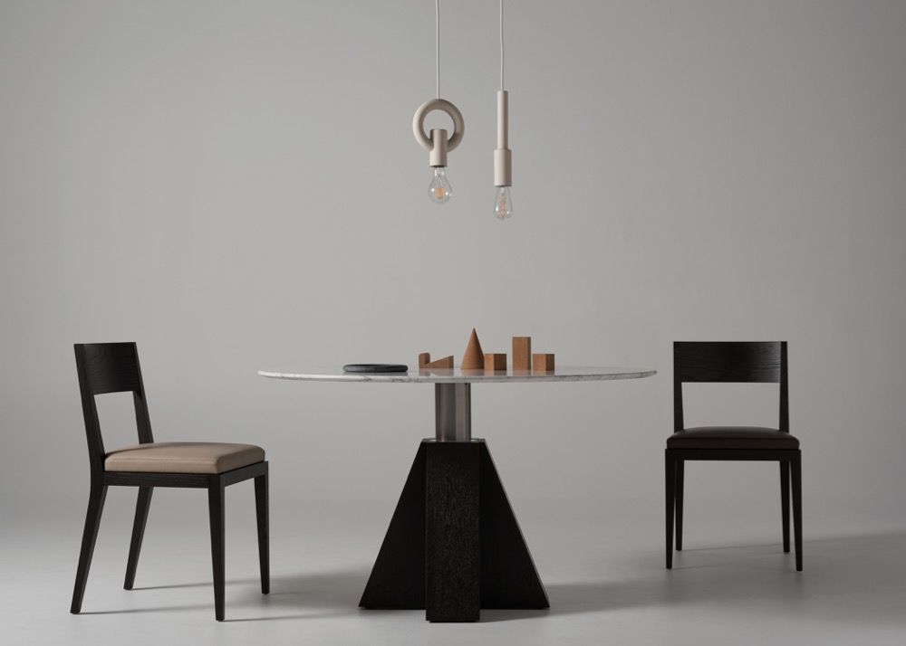 The M table with Carrara marble top and base in black stained oak.Porcelain Bear I-O-N pendant lights in raw porcelain hang over objects in oak, cork &marble.Photograph by Kelly Geddes.