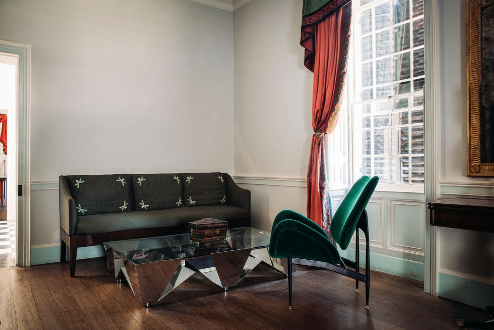 The earliest sofa in Australia shares the limelight in the front room of Old Government House with a mirror polished stainless steel coffee table by Caroline Casey (2007) and a Grant & Mary Featherston designed 'Scape' chair in green velvet (1960).