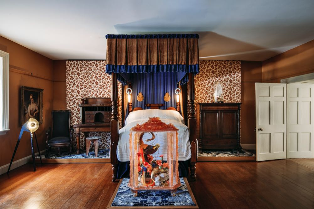 The master bedroom of Old Government House. The narrow four-poster bed houses I-O-N lights by Porcelain Bear. 'Shrink', a floor lamp by  DAAST  (left) illuminates Kate Rhodes'  polyurethane foam &   epoxy resin vitrine ' Pheasant & Pangolin' (2007).