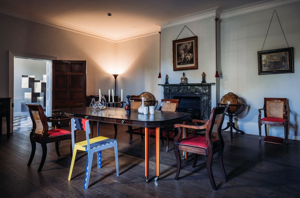 The dining room of Old Government House, resplendent with Adam Goodrum's 'Birds Mouth' table designed for Broached Commissions (2010)along with his folding 'Stitch' chair for Cappellini (2007) and several contemporary decorative pieces.