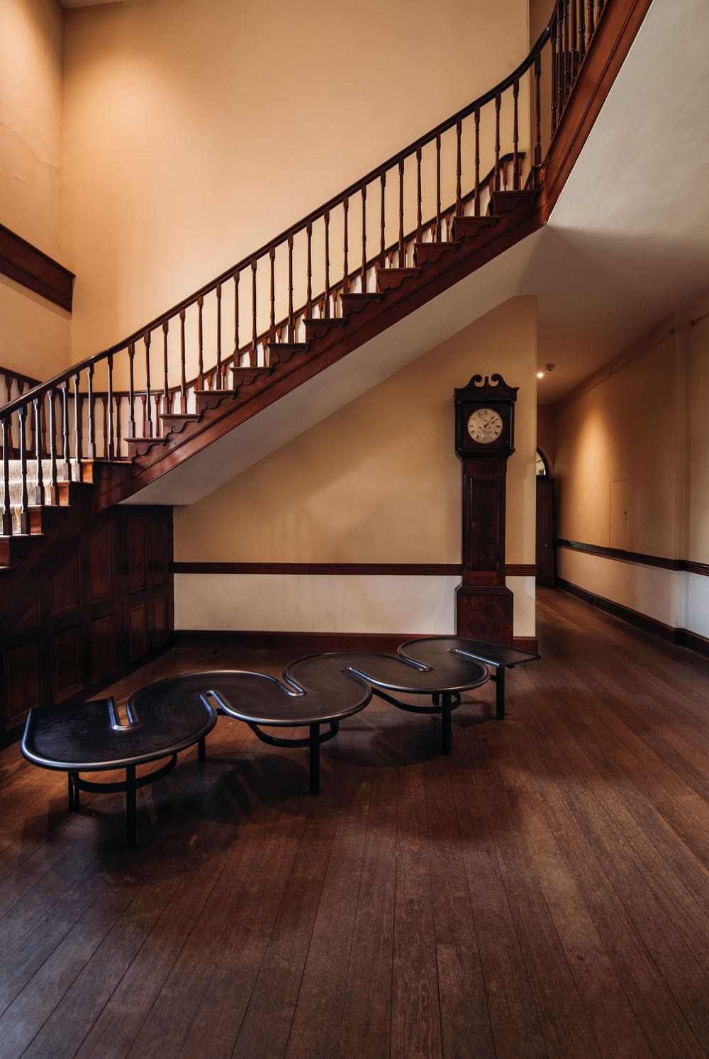 Fred Ganim's 'Plane table' (2016) in the staircase of Old Government House. The grandfather clock is a prized piece of colonial furniture from the Old Government House collection.
