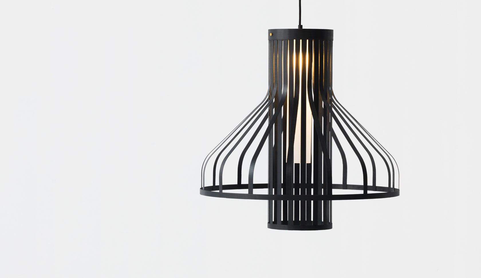 Jamie McLelland's 'Fibre Light Funnel'pendant light for New Zealand brand Resident. Thin strips of carbon fibre are peeled from the central cylinder to create an incredibly lightweight and overtly graphic pendant light.