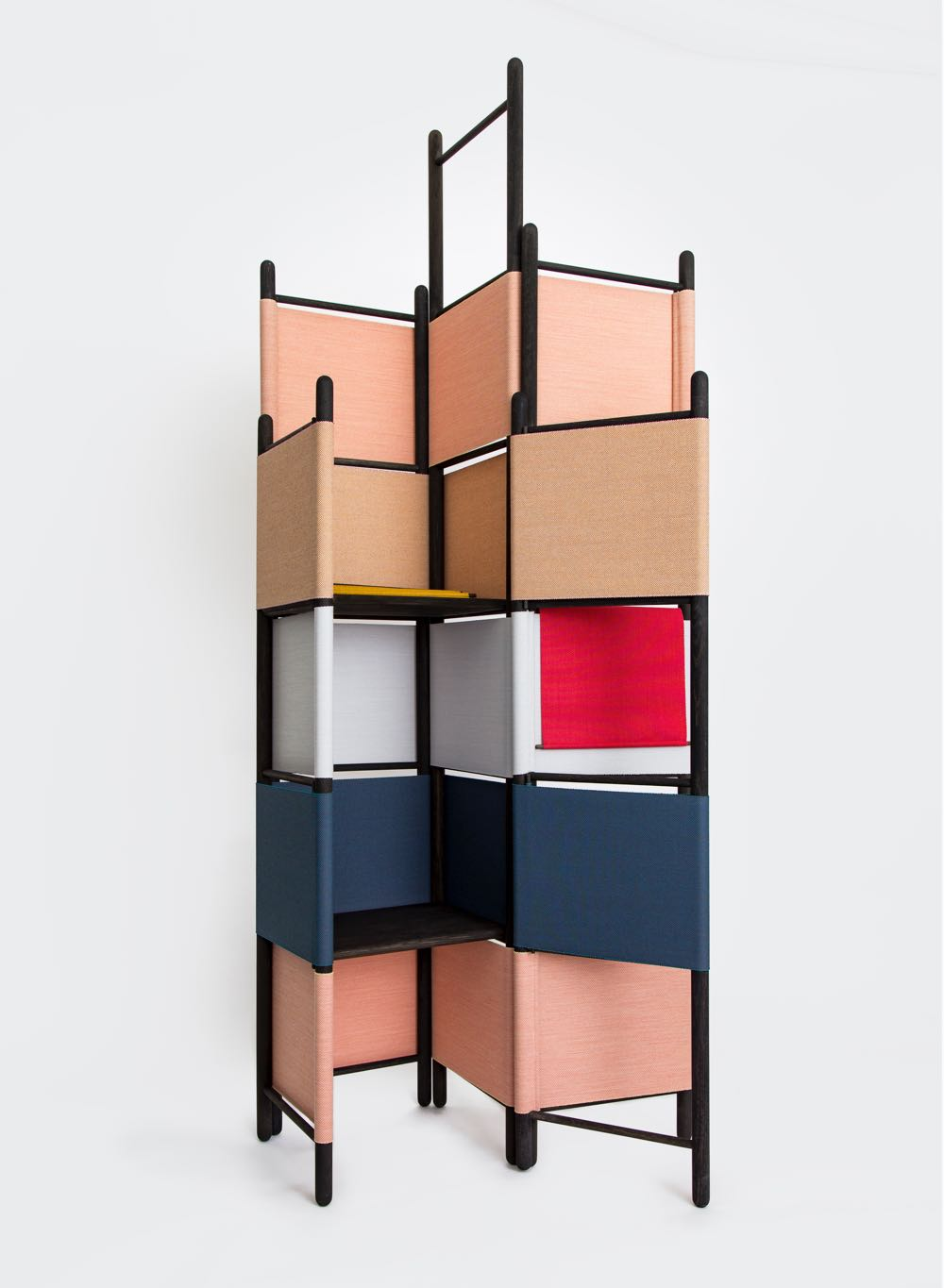 Rive Roshan's 'Loom Bound' screen in black with Kvadrat fabric. The frame is held together and in position by the tightly wrapped fabric. It offers small shelf compartments as well as acting as a room divider / screen.