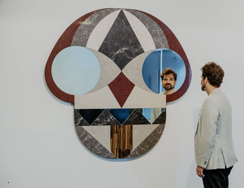 Hayon's mask-like wall pieces combine matt stone-like surfaces with segments of mirror.  Photography by Vicky Lam.