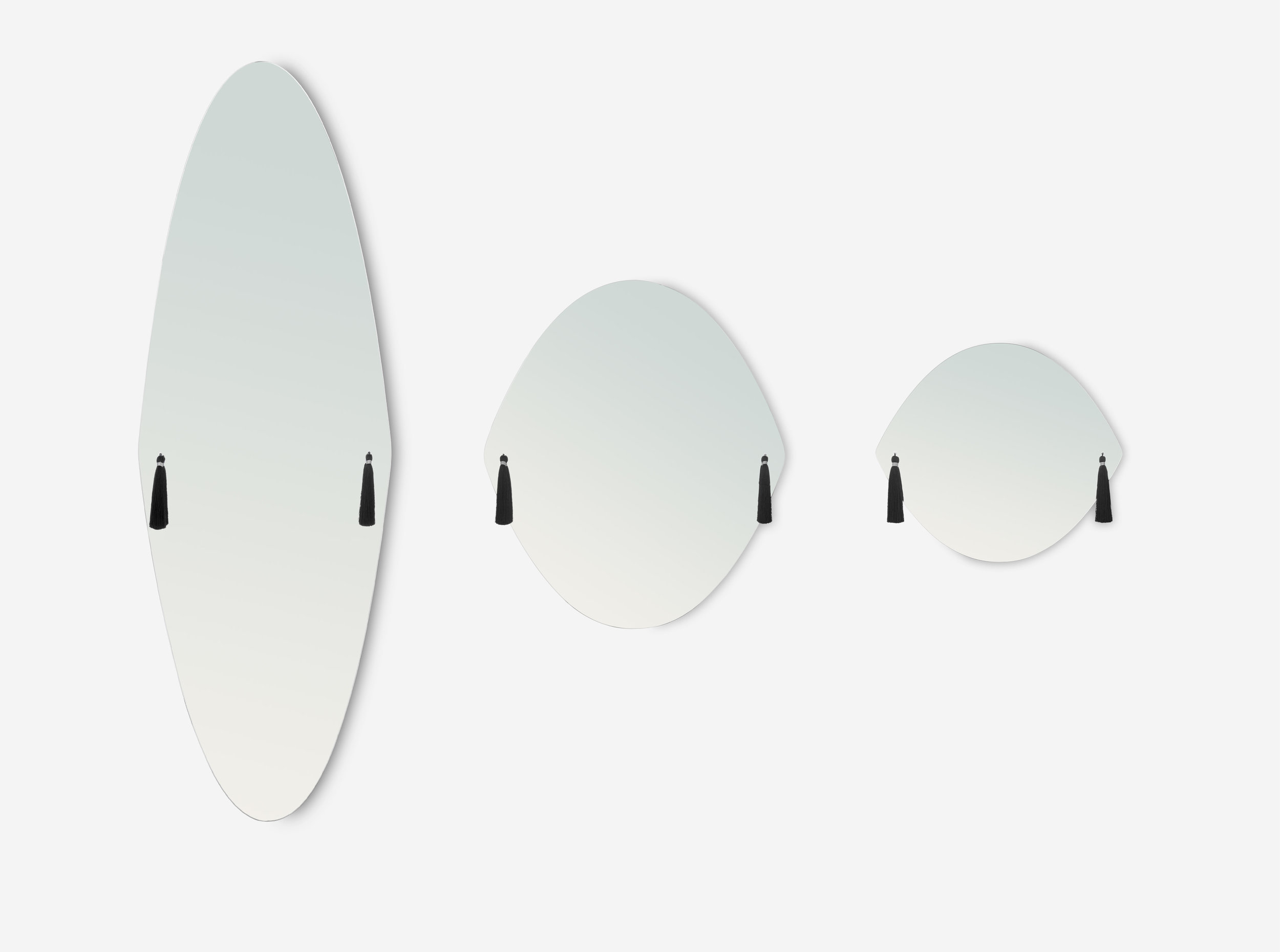 The 'Panache'mirrors by Constance Guisset for French label Petite Friture. The mirrors are available in the three shapes shown and feature tassels in a choice of colours.