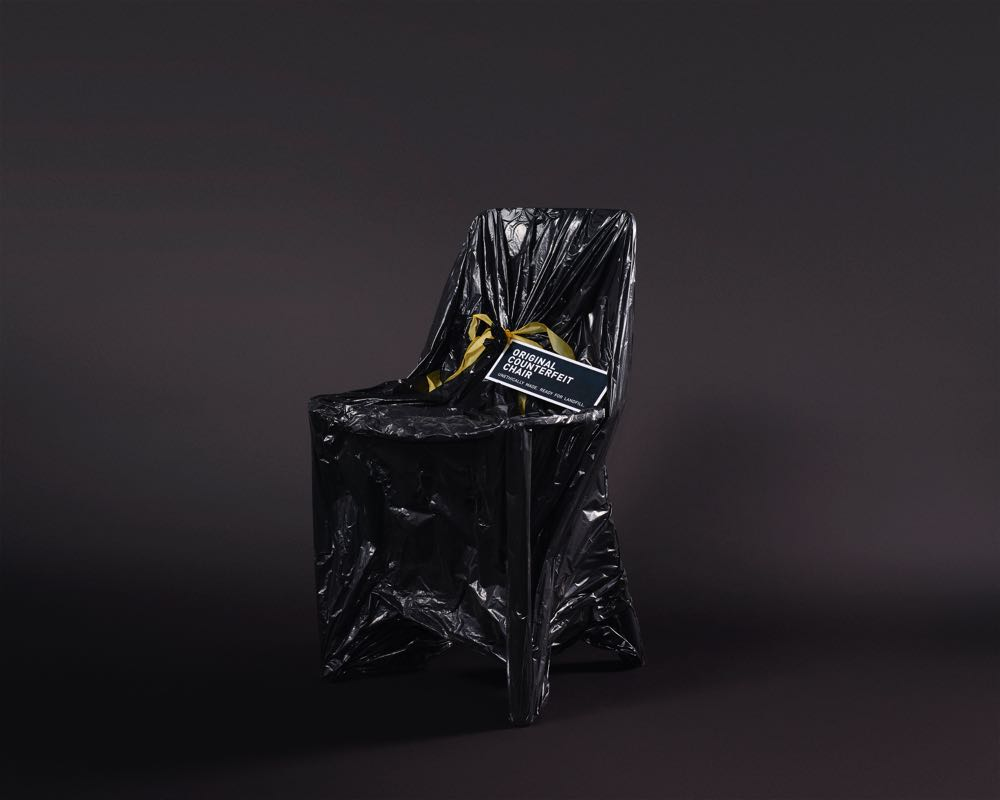"""Adam Goodrum's offering in the exhibition  Original Fakes . A replica 'Hal' chair is shrouded in a plastic garbage bag and given a label: """"Original Counterfeit Chair: Unethically Made, Ready for Landfill"""""""