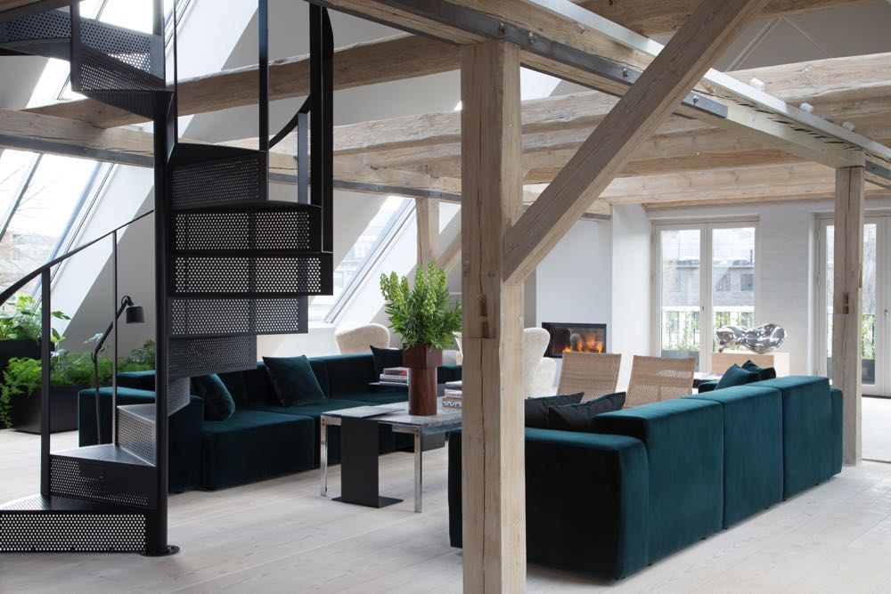The light-filled lounge area of the Vipp 'Loft' with its metal spiral staircase and restored timber beams.