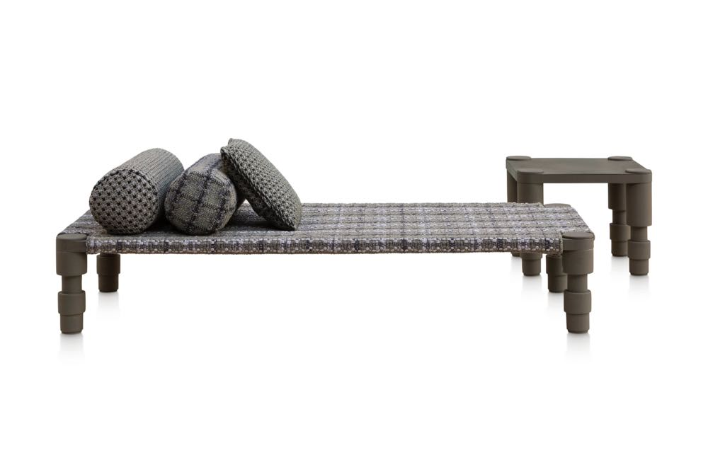 Patricia Urquiola  added to her 'Garden Layers' collection of outdoor cushions and rugs for Spanish brand  GAN  with two furniture pieces - a daybed and side table - in lacquered aluminium. They feature boldly turned legs and the collections extraordinary textured woven outdoor fabrics.