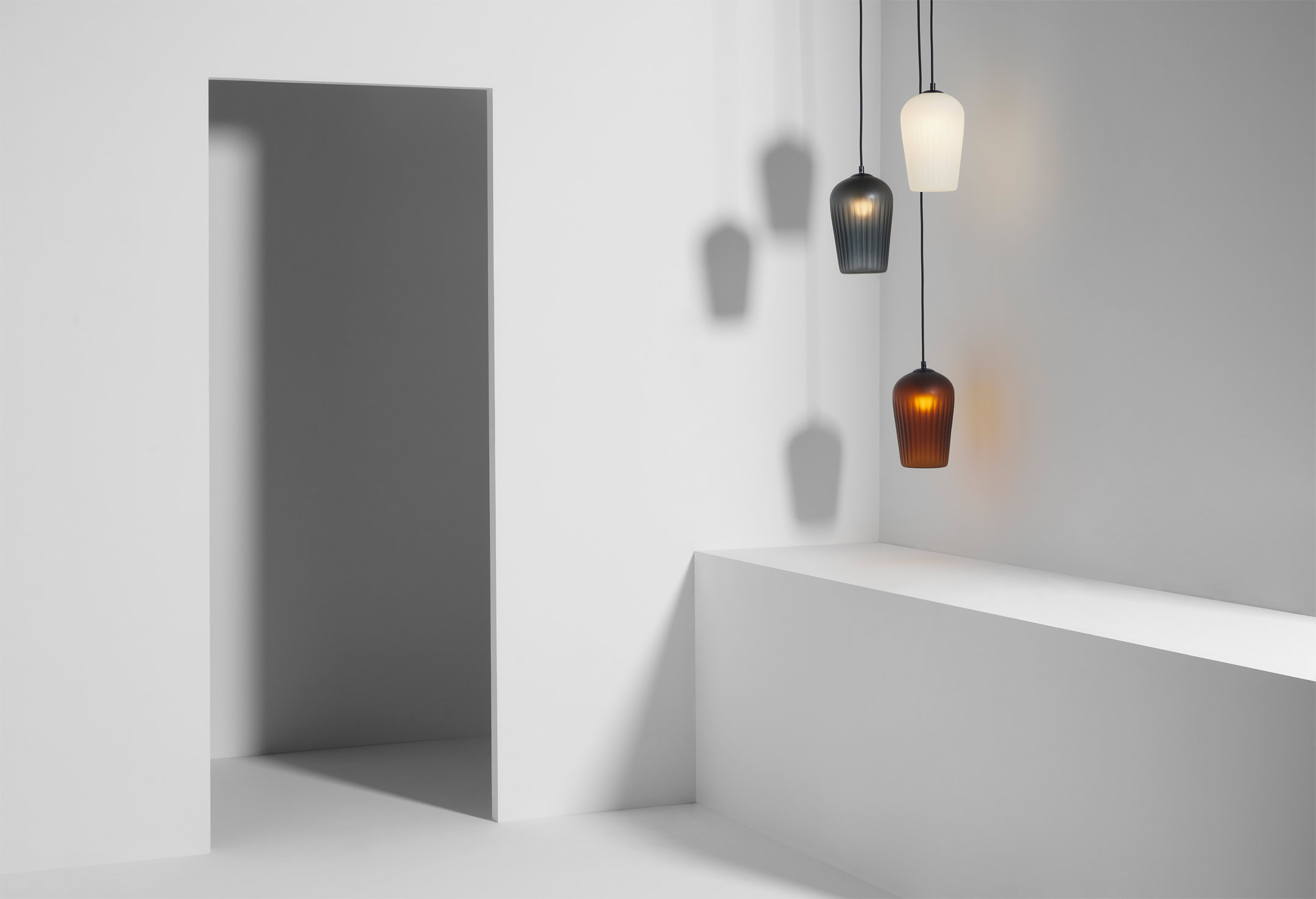 Lumil's 'Blend' pendants in heavy blown glass. The flower bud shape is excentuated by verticals ribs and is available in numerous colours.