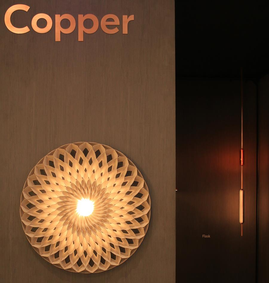 The front of the Copper Design stand featuring their now famous 'Sun'wall light and their new 'Flask' light in the background.