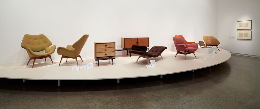 B220H-Curl-up-Contour (left), cabinets made by Kennett Bros & Rayner, the Z300 Contour lounge from 1953, the E1 Eleanor Contour elastic suspension armchair (in pale red) from 1954, and on the far right the Town House chair from 1956.