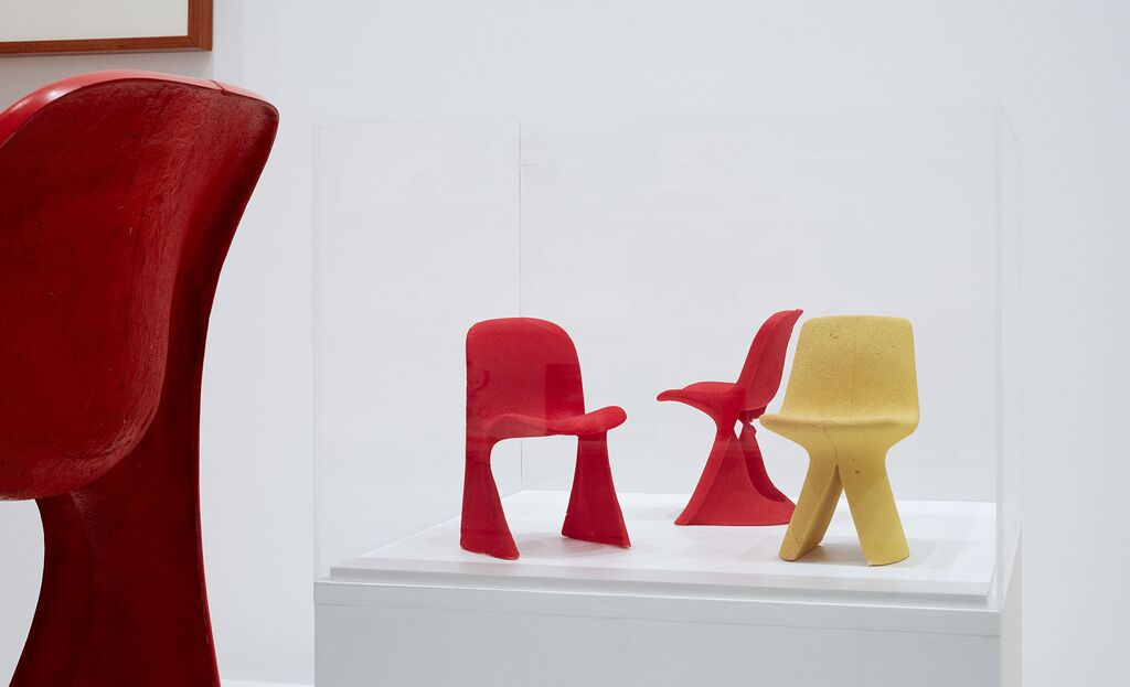 A fibreglass prototype of the 73 chair coming into frame (left) and three maquettes of injection moulding ideas from that time.