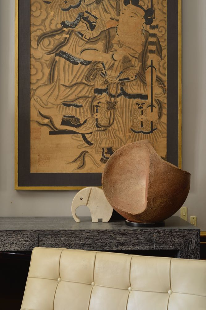The apartment of Michael Coorengel & Jean-Pierre Calvagrac in the 2nd arrondissement of Paris. The delicacy of a Oriental artwork is counteracted by an Fili Mannelli elephant in travertine and a ceramic sculpture.
