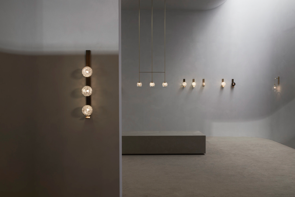 Interior of the Articolo stand at Euroluce featuring a triple ball Fizi wall sconce in bronze in the foreground. The space had a monastic quality with extremely etherial light. Photography by Willem-Dirk du Toit.
