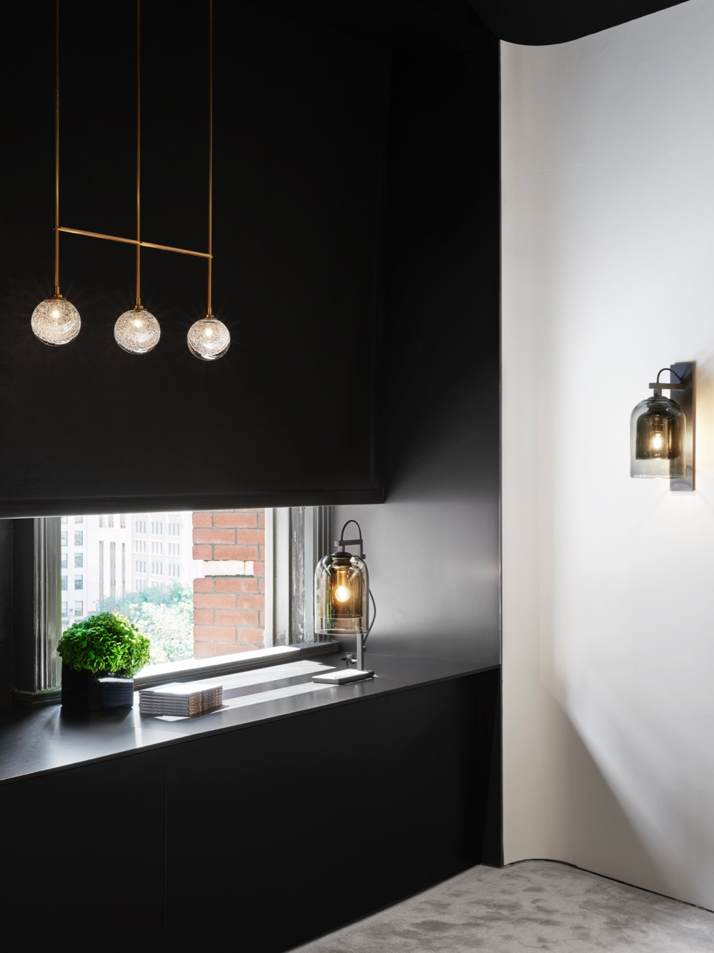 The Articolo New York showroom showing the Fizi Triple ball brass rod pendant and the Lumi table lamp and wall sconce. Photograph: Brooke Holm.