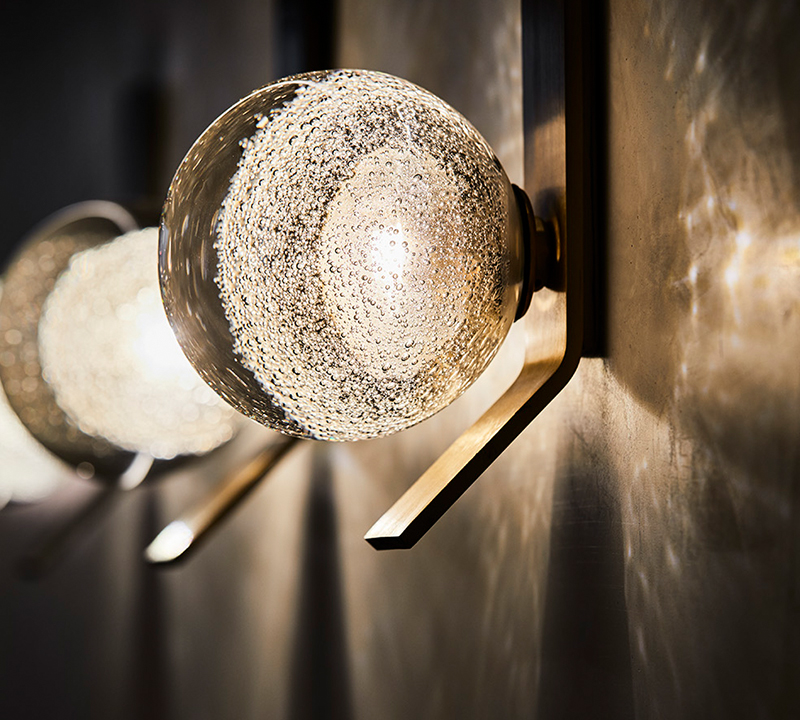 The Fizi wall sconce with kick from Articolo. The fitting features a solid brass bar and heavy glass sphere with random bubbles that cast beautiful patterns on surrounding walls.