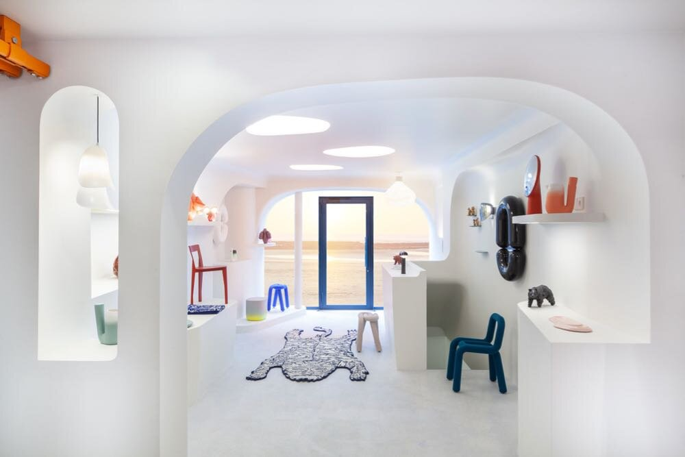 The all white end of the Moustache store with a plethora of gentle arches and round skylights creating a soft background for the colourful objects to jump out of.