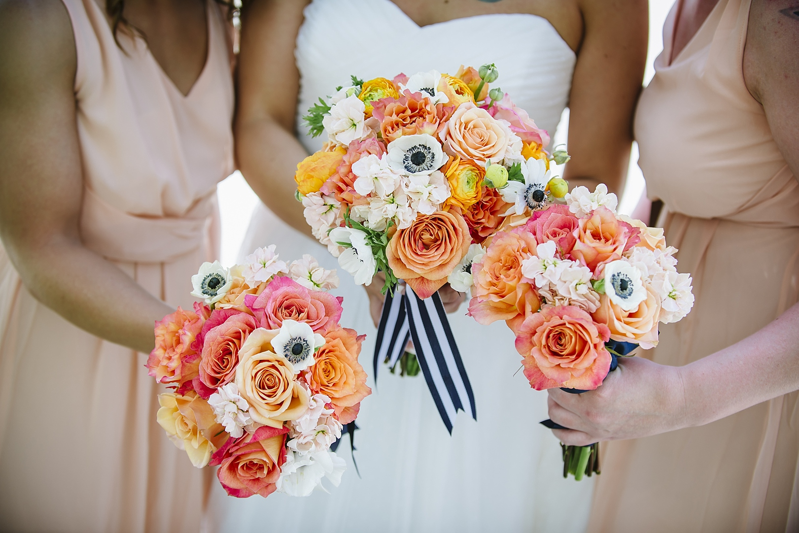 bright pink and orange garden rose wedding bouquet with striped ribbon