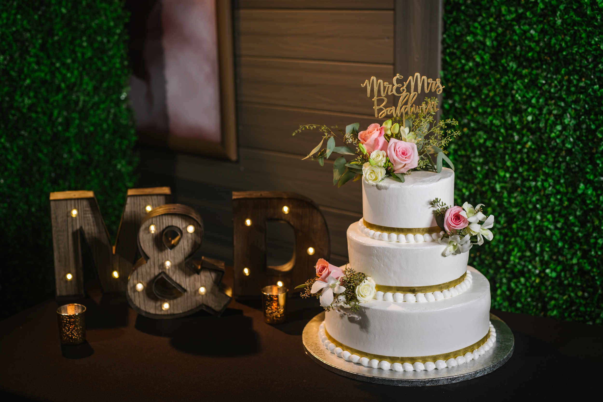 tampa-wedding-photographer-hotel-zamora-three-tier-cake-gold-lights-green-pink-flowers-calligraphy-topper