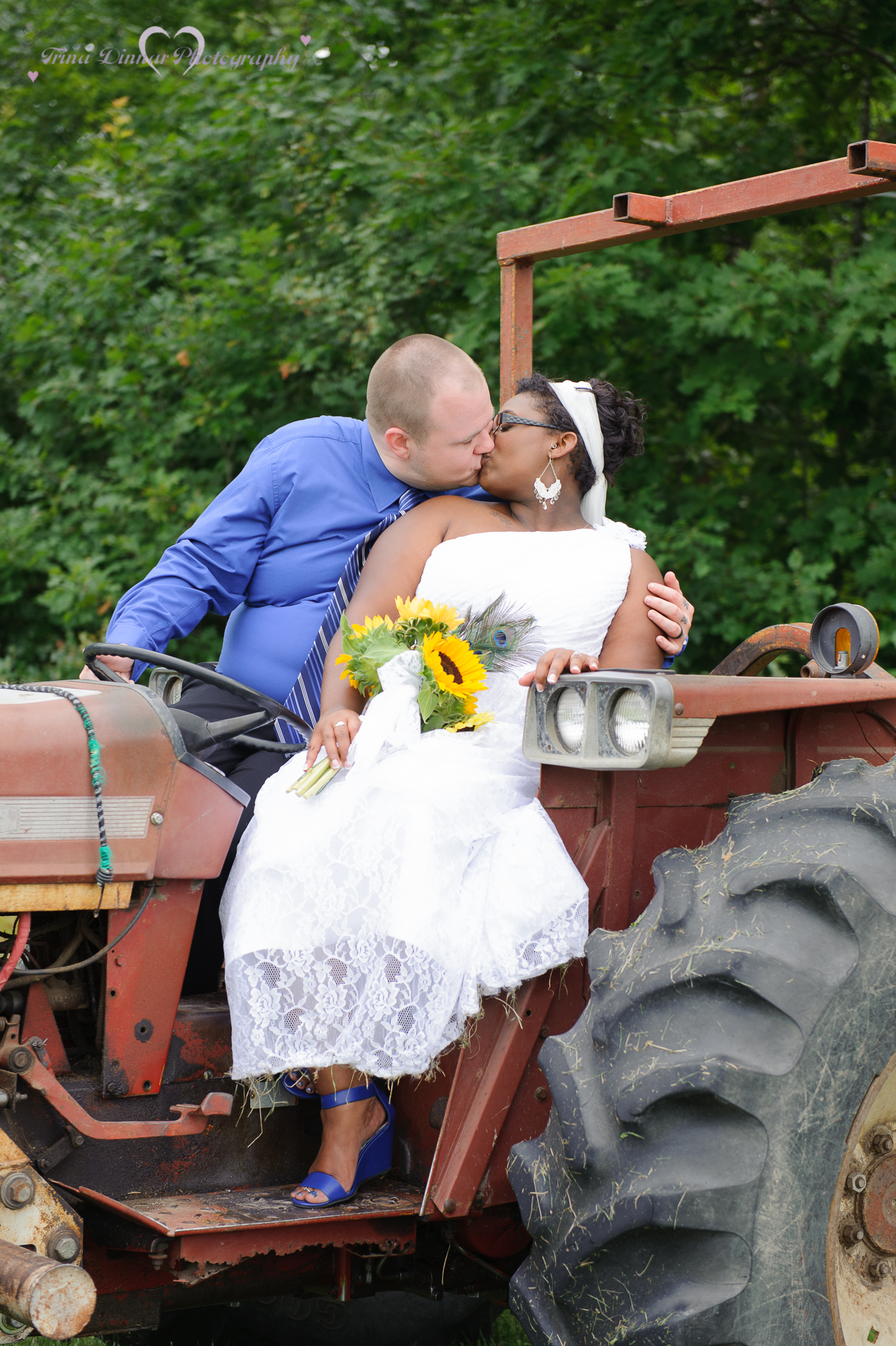 couple kiss on a tractor during their wedding in maine