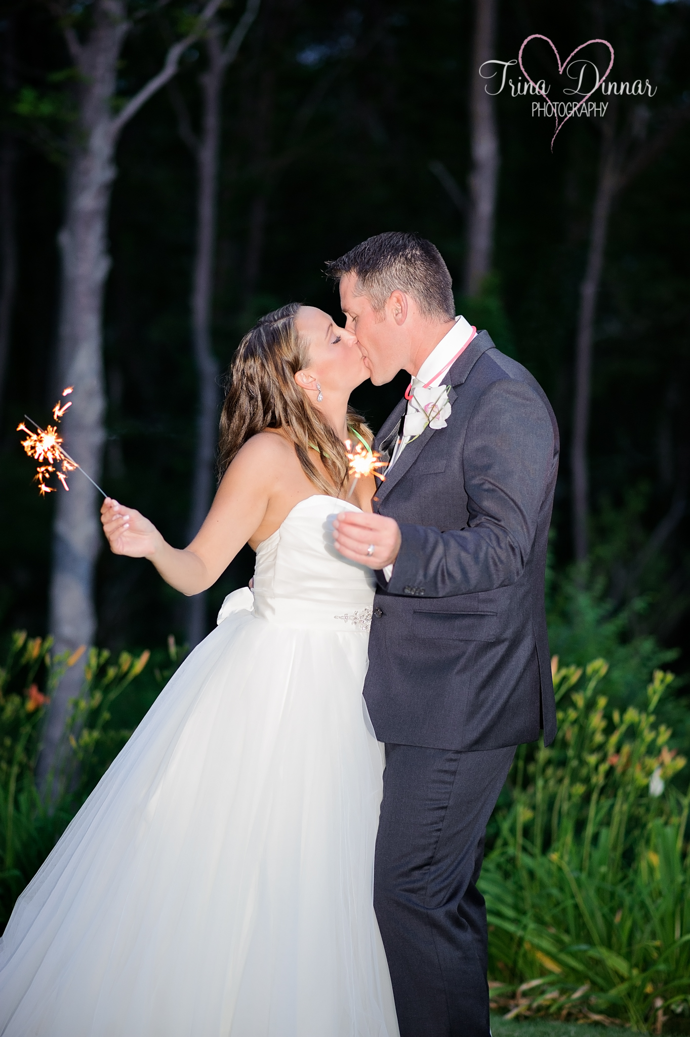 Couple share a kiss with their wedding sparklers