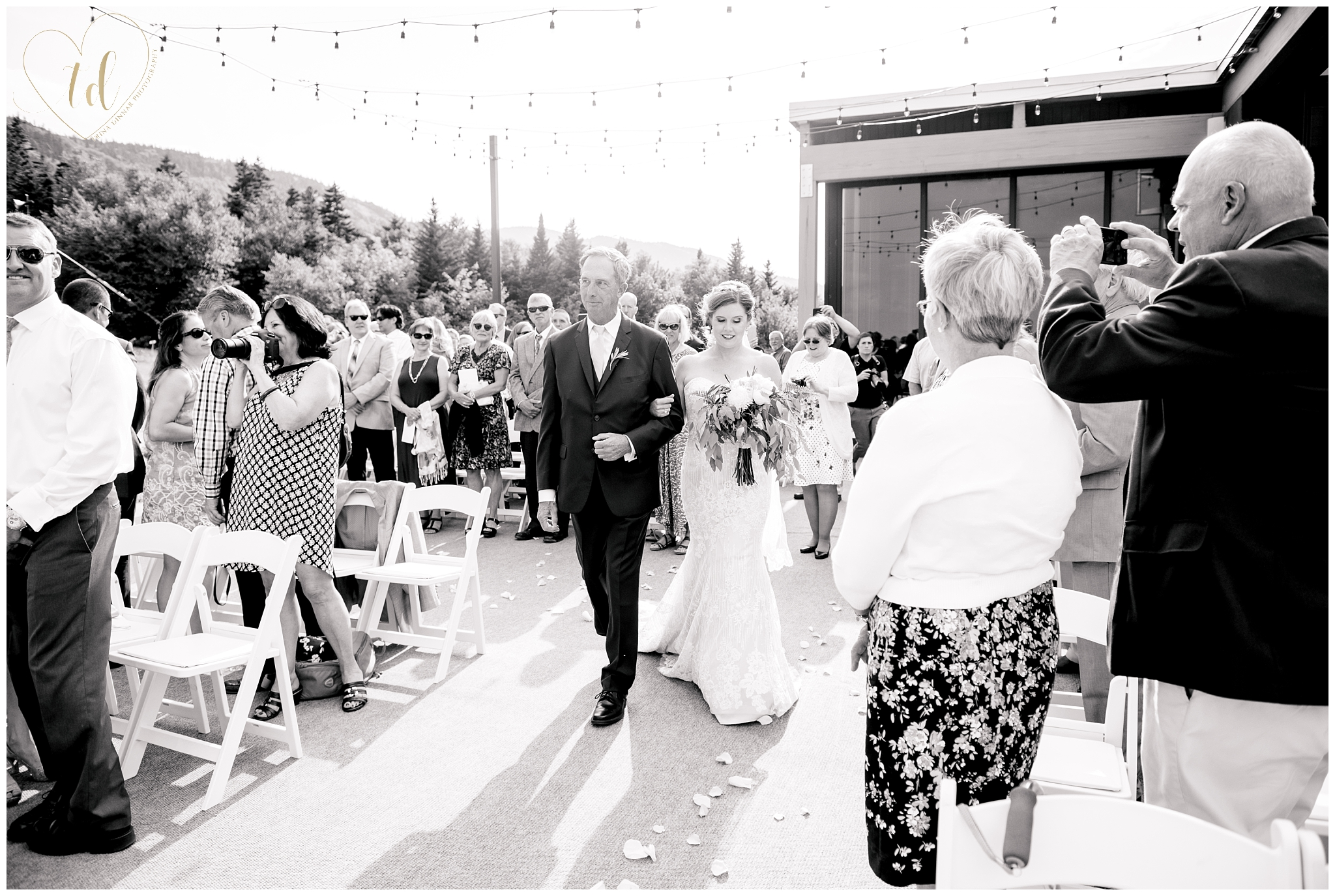 Bride walks down the aisle with her father at Sunday River's Peak Lodge.