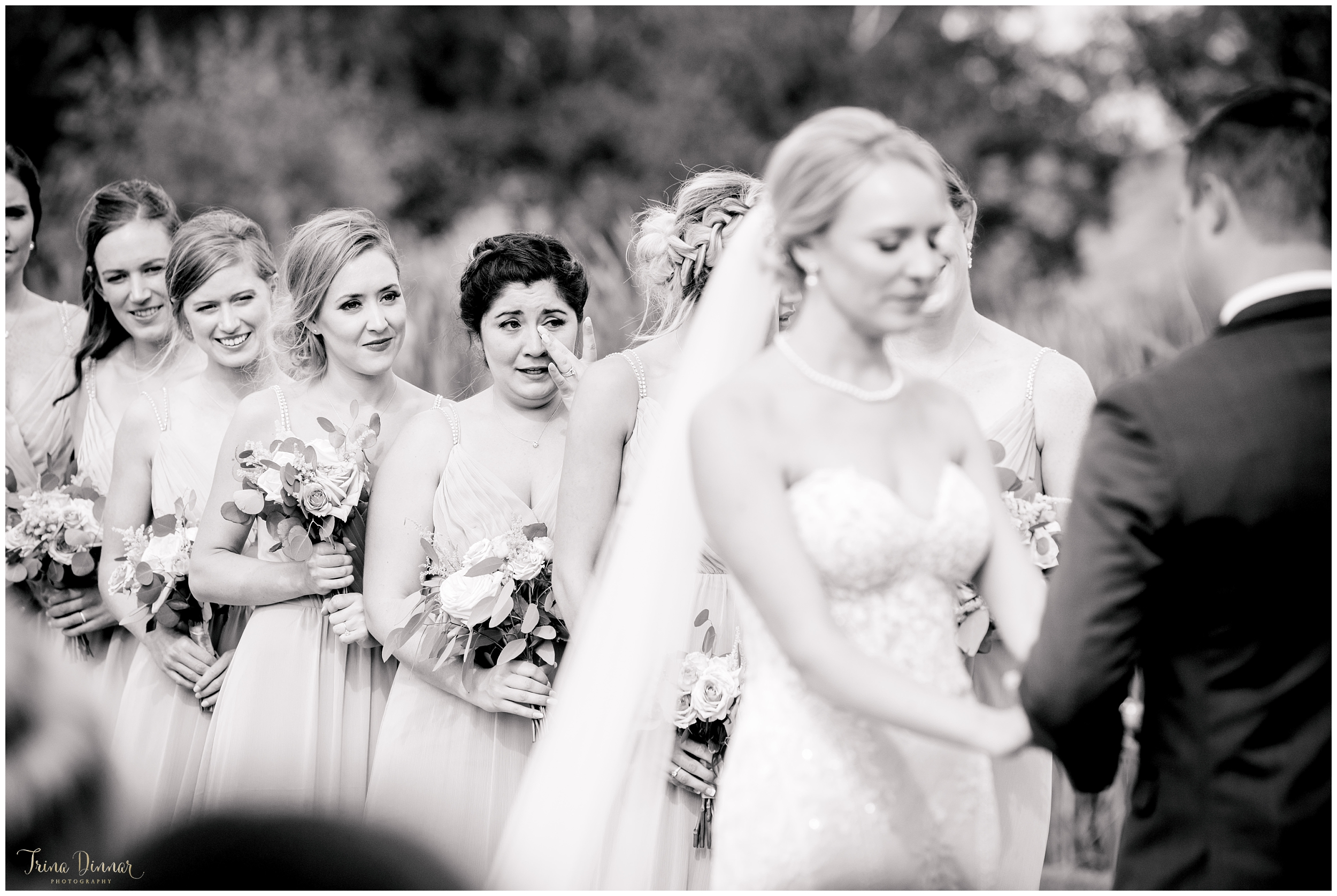 Documentary wedding photographer captures Bridesmaid's emotional moment during ceremony in Maine.