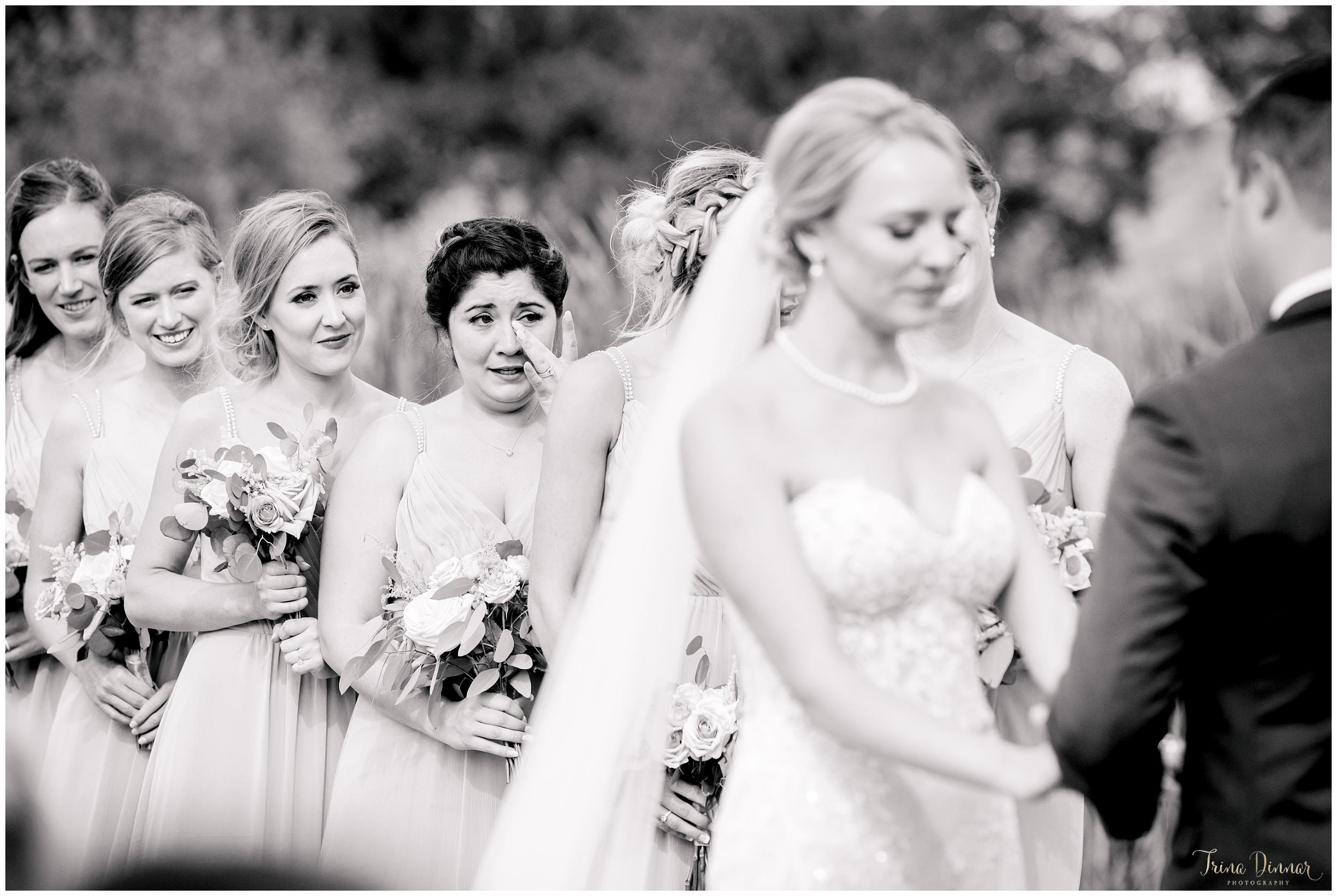 Photojournalist Maine Wedding Photographer captures emotional bridesmaid during ceremony.