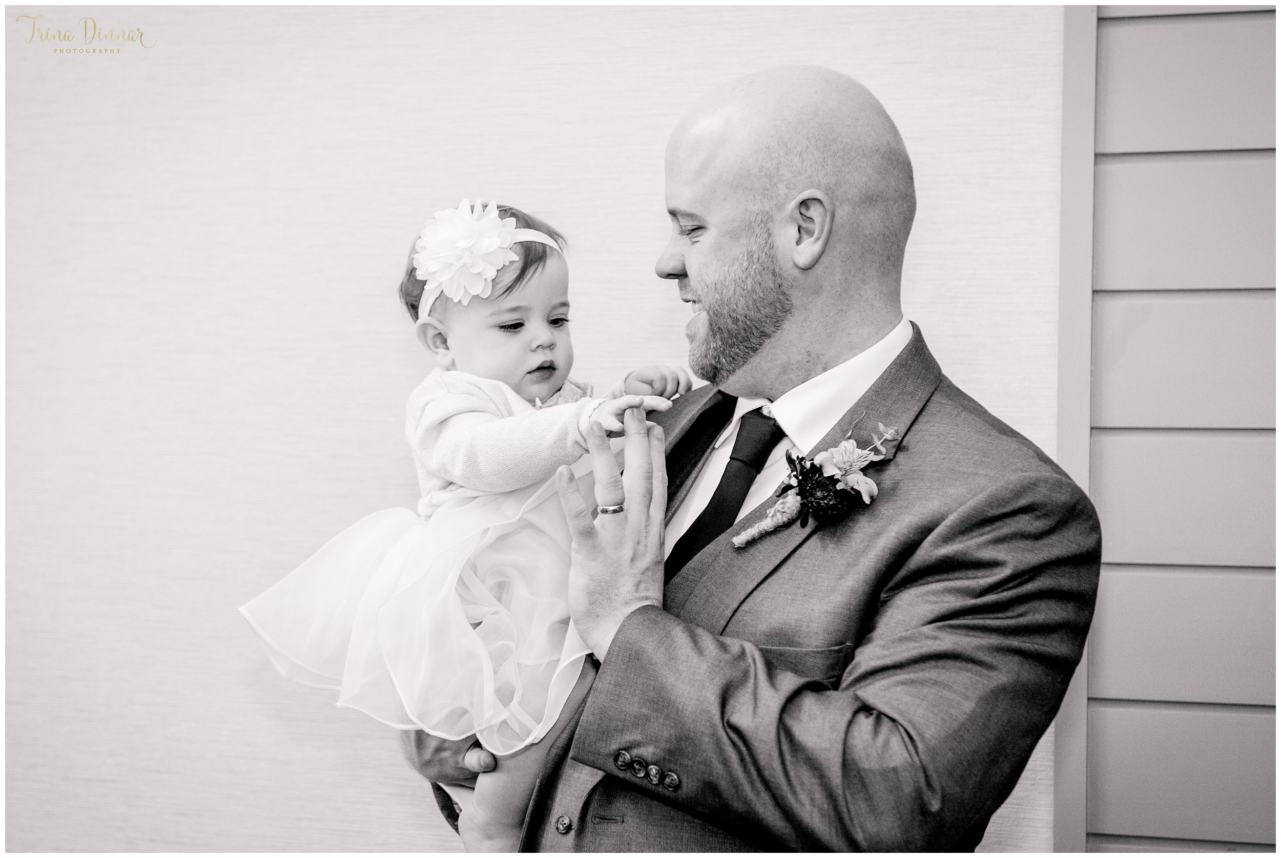 Groomsmen shares a moment with adorable baby girl