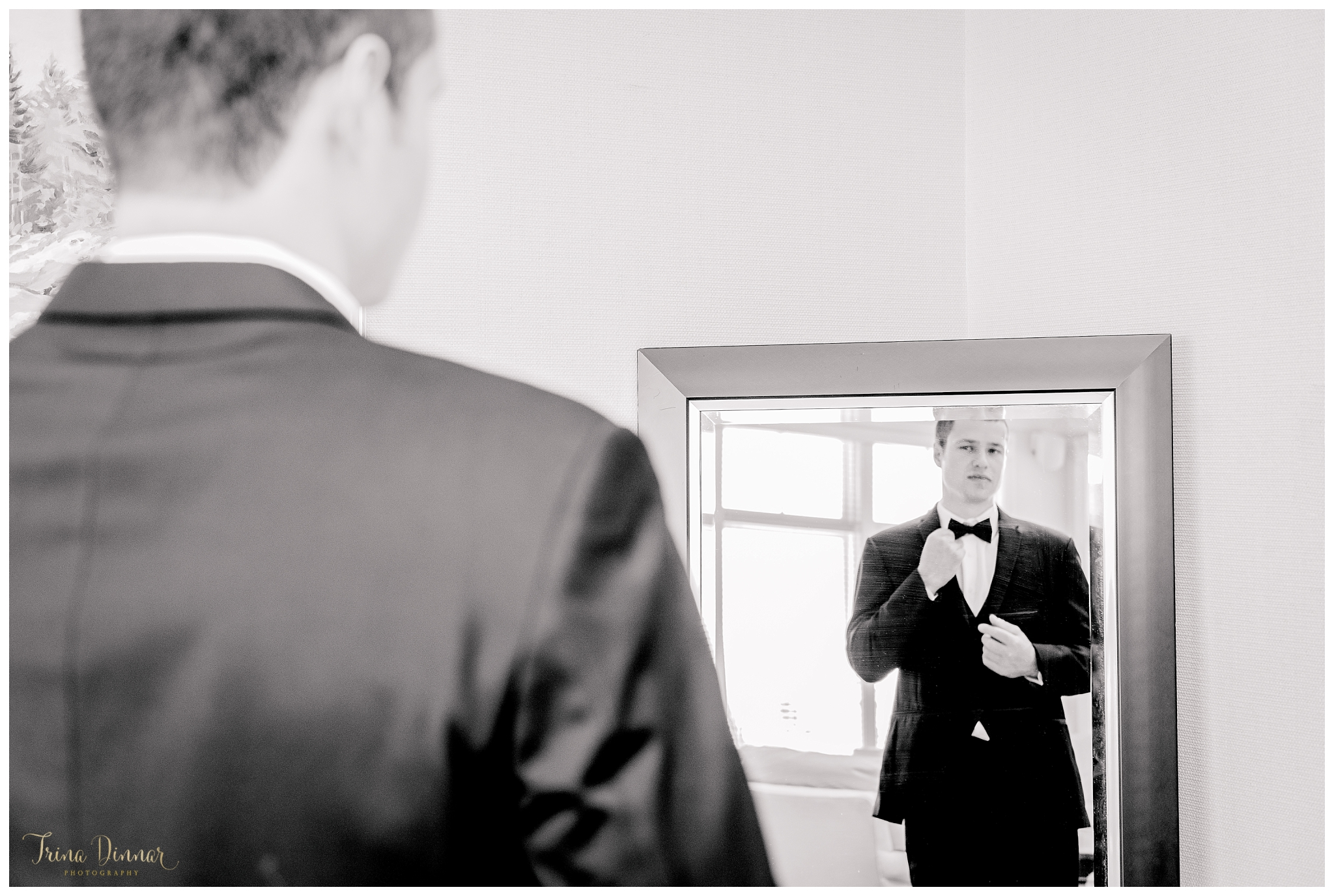 Groom fixing his tie and jacket in the mirror at The Summit.