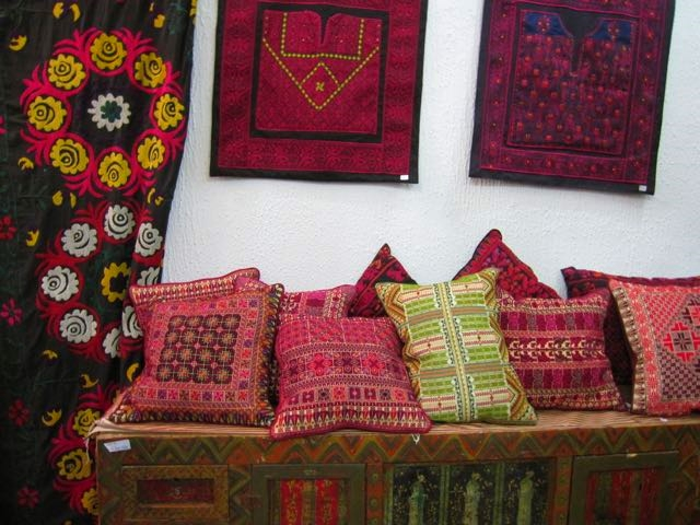 These are definitely textiles. Suzani embroidery, left, and Palestinian cross-stitch pillows and bodice pieces, in Amman, Jordan.