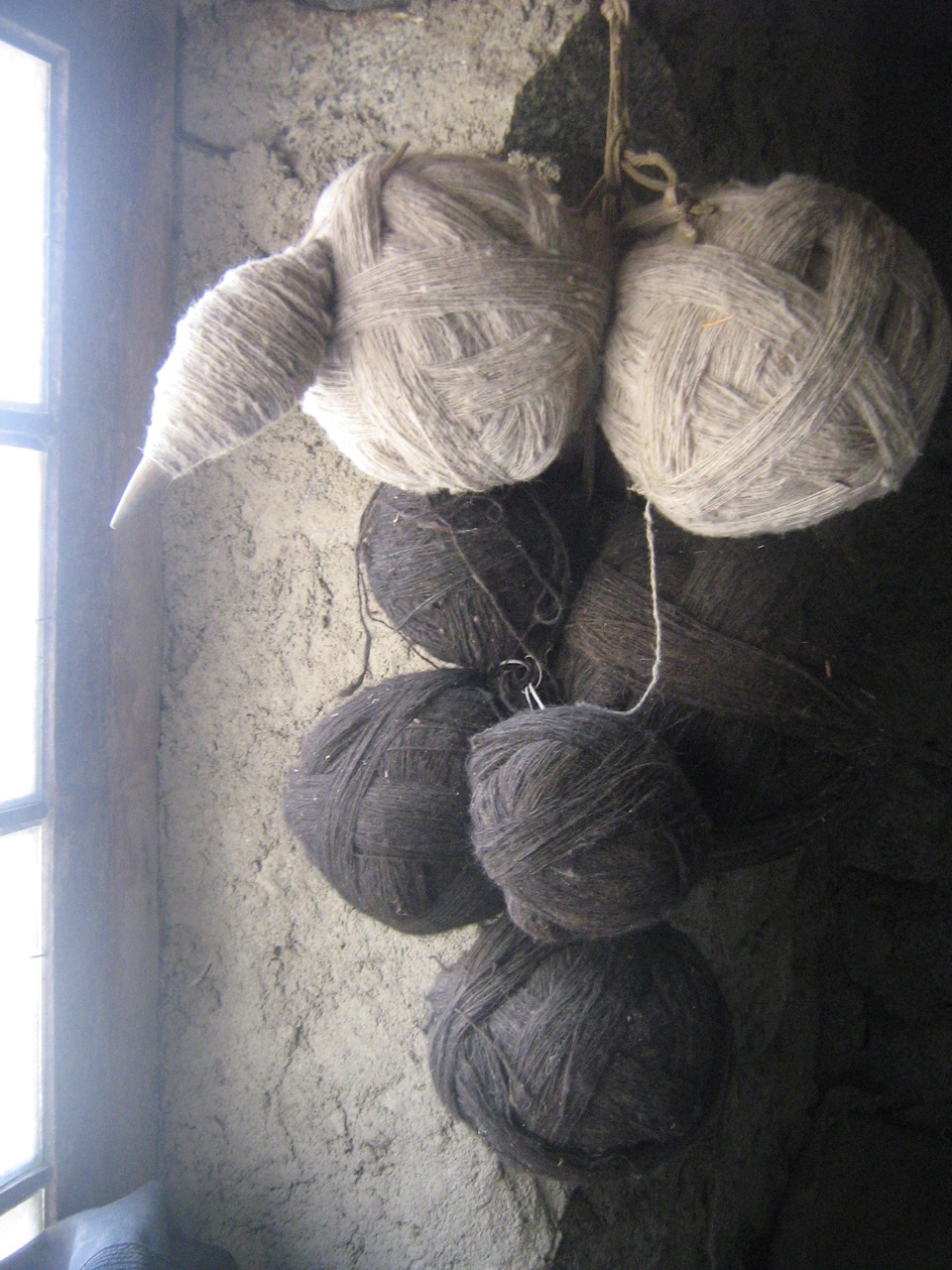 Two-stranded plying balls of spindle-spun yarn and a phang-in-progress, hanging in a Ladakhi home in 2007.