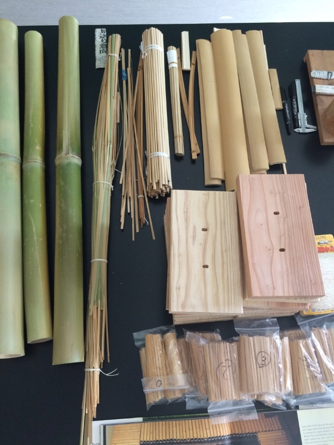 Workshop materials: whole Aodake, higo strips, blocks of hinoki for supporting reeds-in-progress, and packets of prepared reeds.