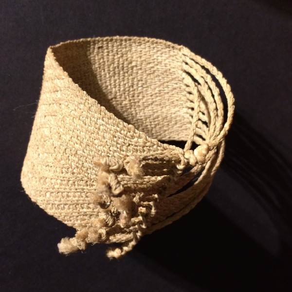 Finished cuff with fringe threaded through loops.