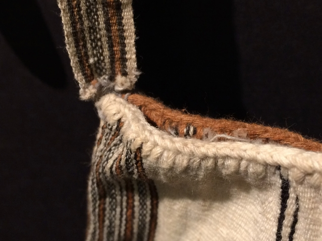 Bag detail, showing a cross knit looping edging around the top. Naturally colored cotton.